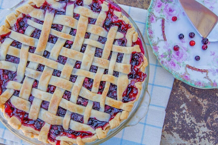 huckleberry pie with lattice top and a plate with huckleberries