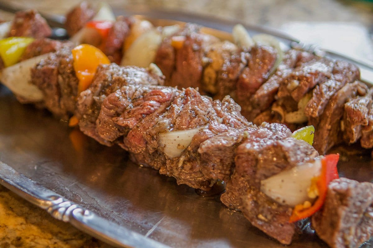 raw shish kabob on skewers on a tray