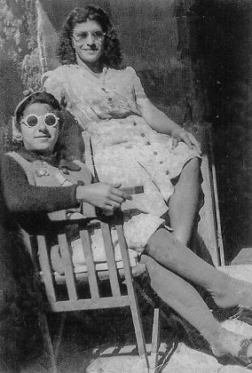 old black and white photo of a lady sitting in a chair and her friend sitting above her