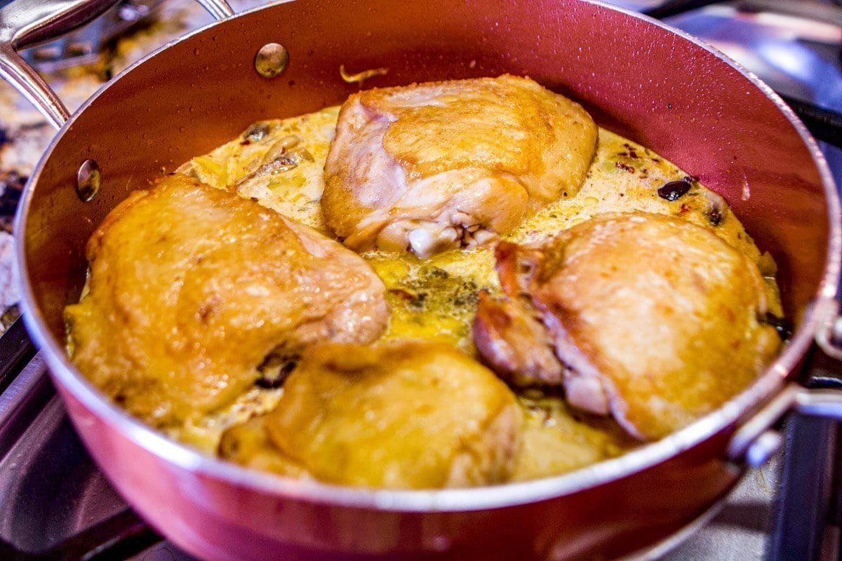 chicken cooking in a pan with sauce