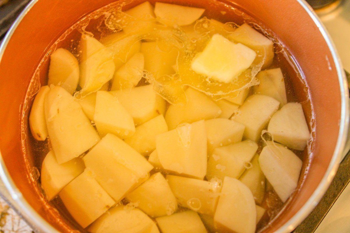 chopped potatoes and a tab of butter in a saucepan