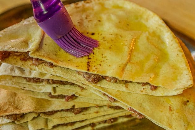stuffed pita bread being brushed with oil