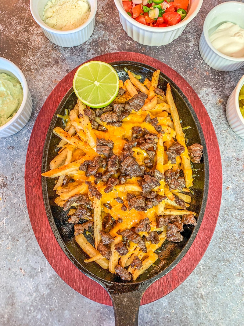 Carne Asada fries on a hot pan with fixings