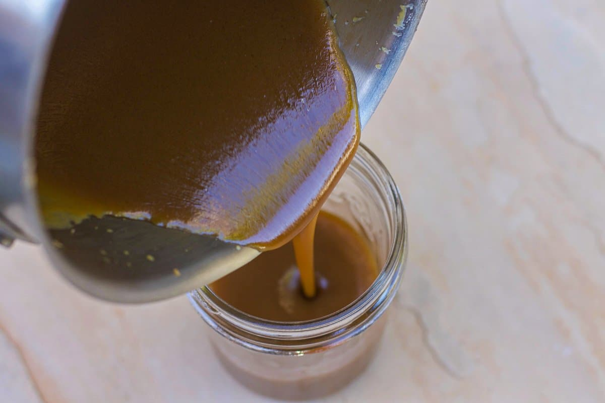 pouring caramel sauce in a jar