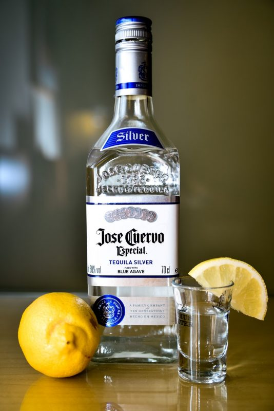 tequila bottle with lemons and a glass