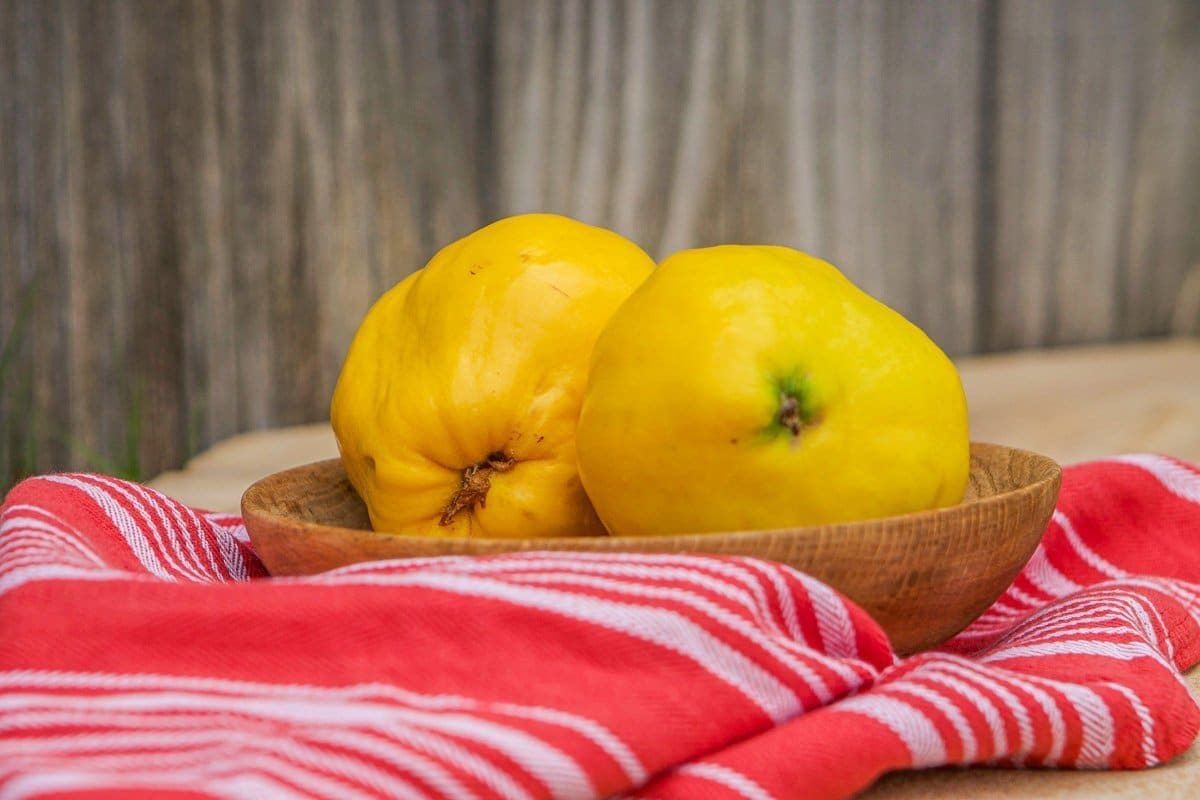 fruit in a wooden bowl on a red dish cloth