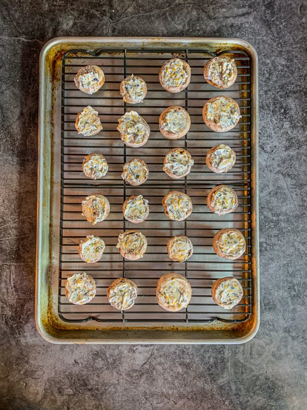 stuffed mushrooms on a rack over a cookie sheet