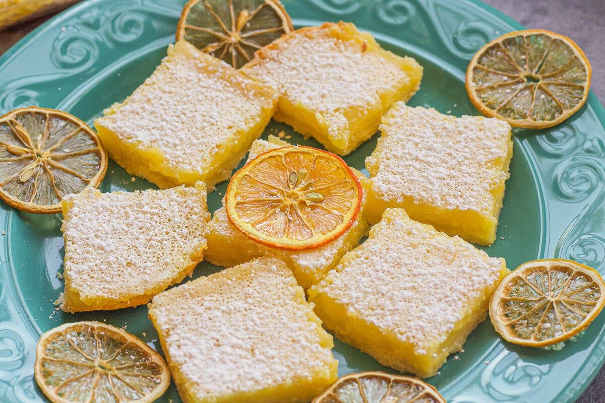 lemon bars on a plate with lemon slices around them