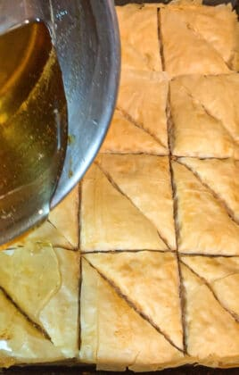 pouring syrup over baklava
