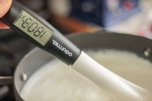 checking yogurt temperature with a thermometer