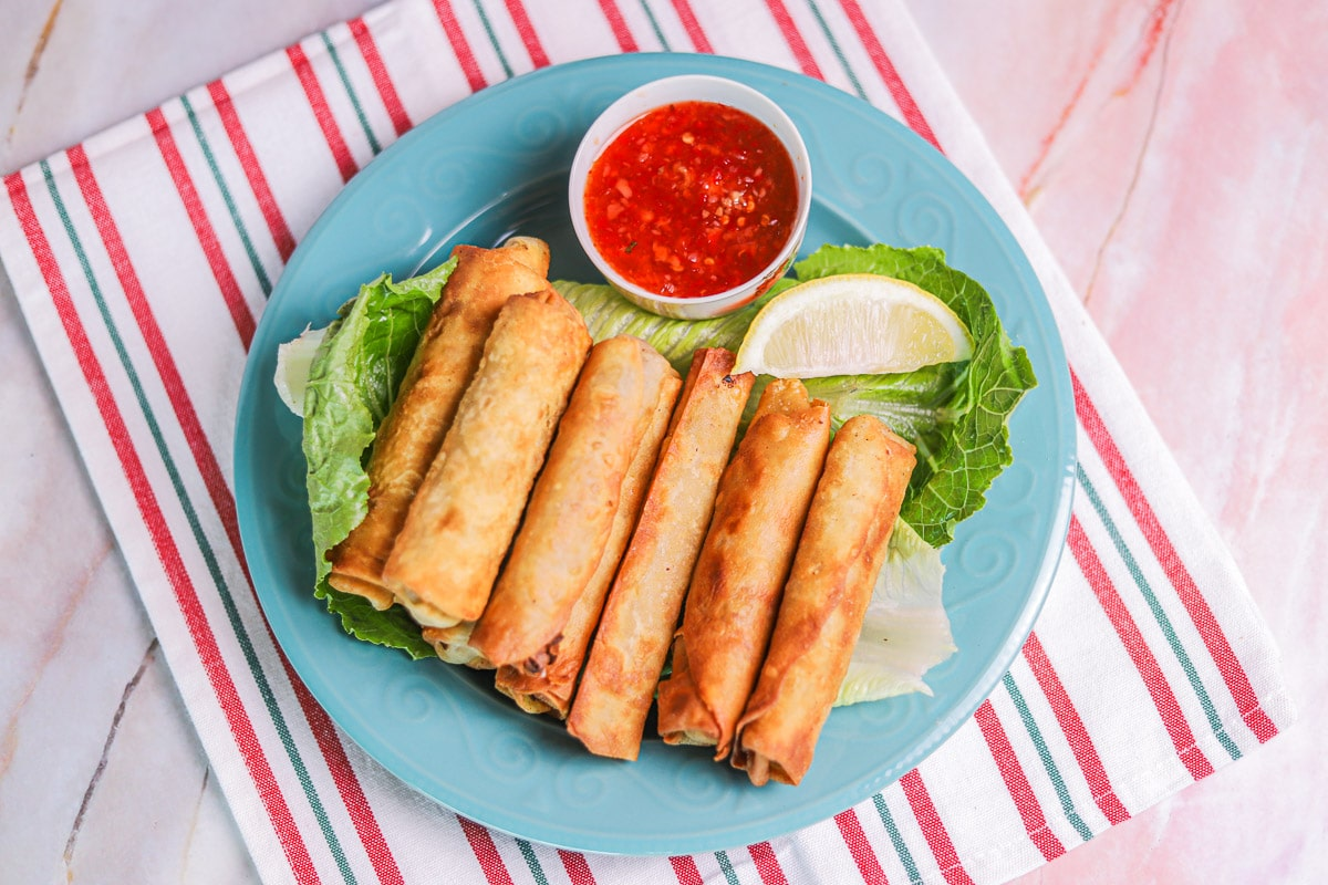 lumpia on a plate with sauce and a wedge of lemon