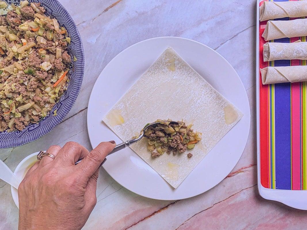adding filling inside egg roll wrapper