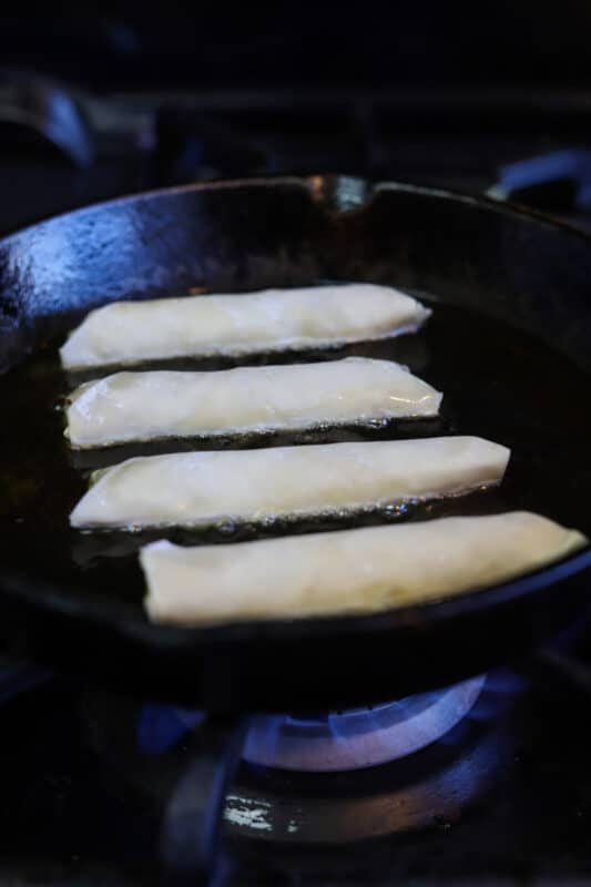 lumpia being fried in a pan