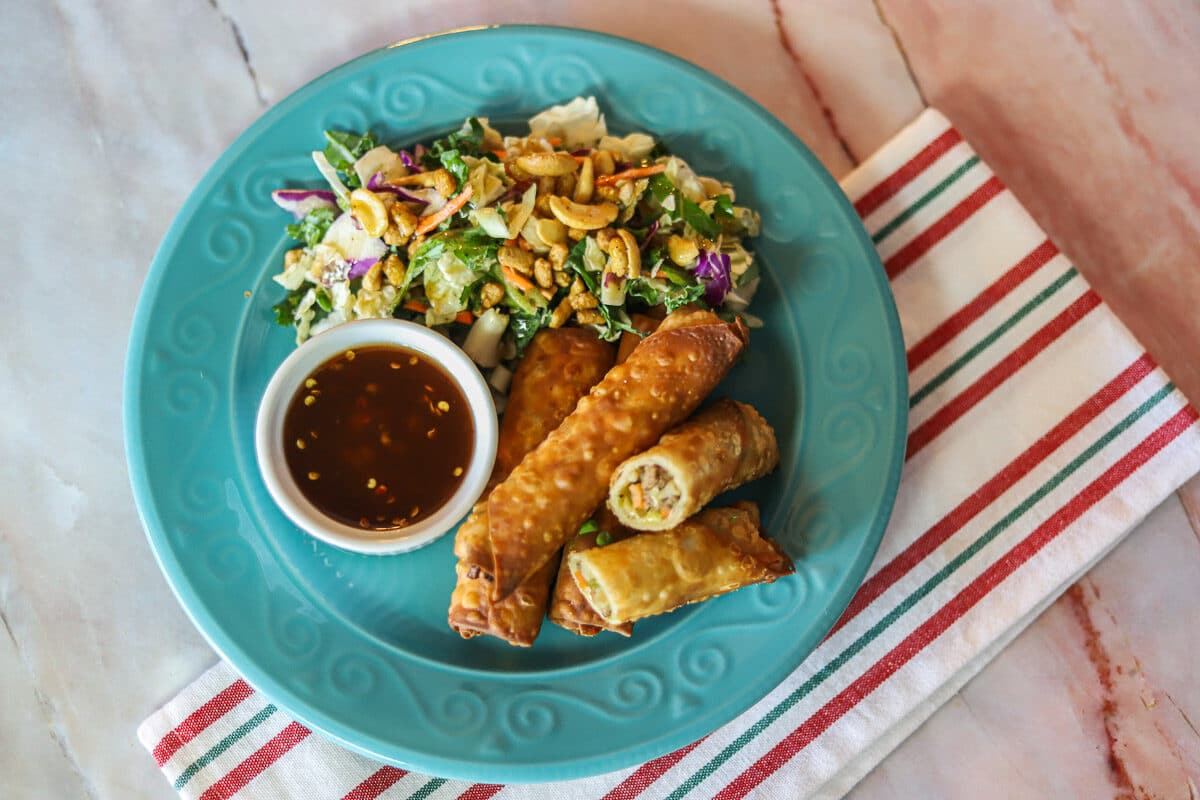 eggrolls, salad, and sauce for dipping on  blue plate