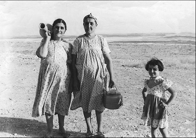 two ladies holding old jars with a little girl standing by them in a field
