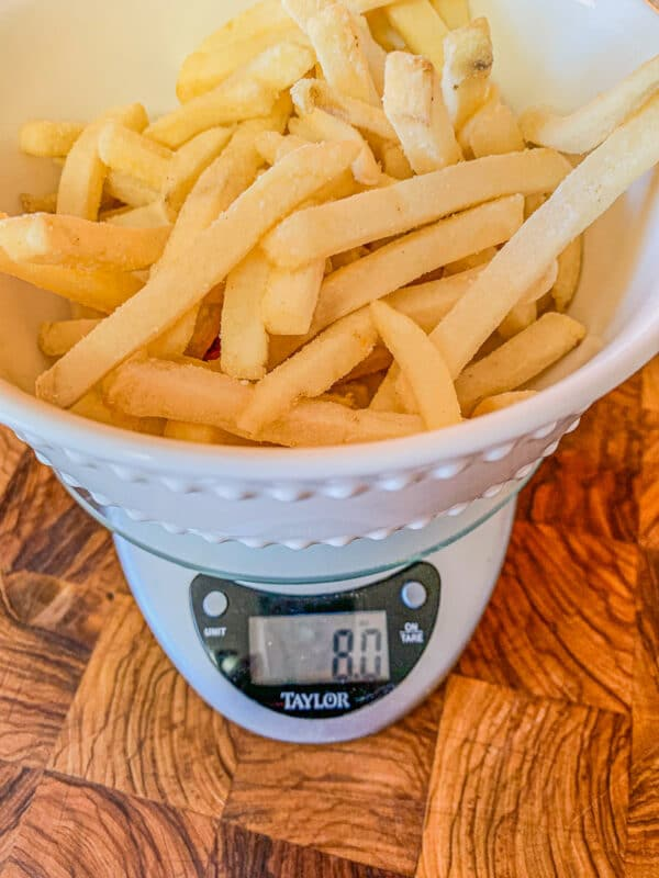 fries being weighed on a kitchen scale
