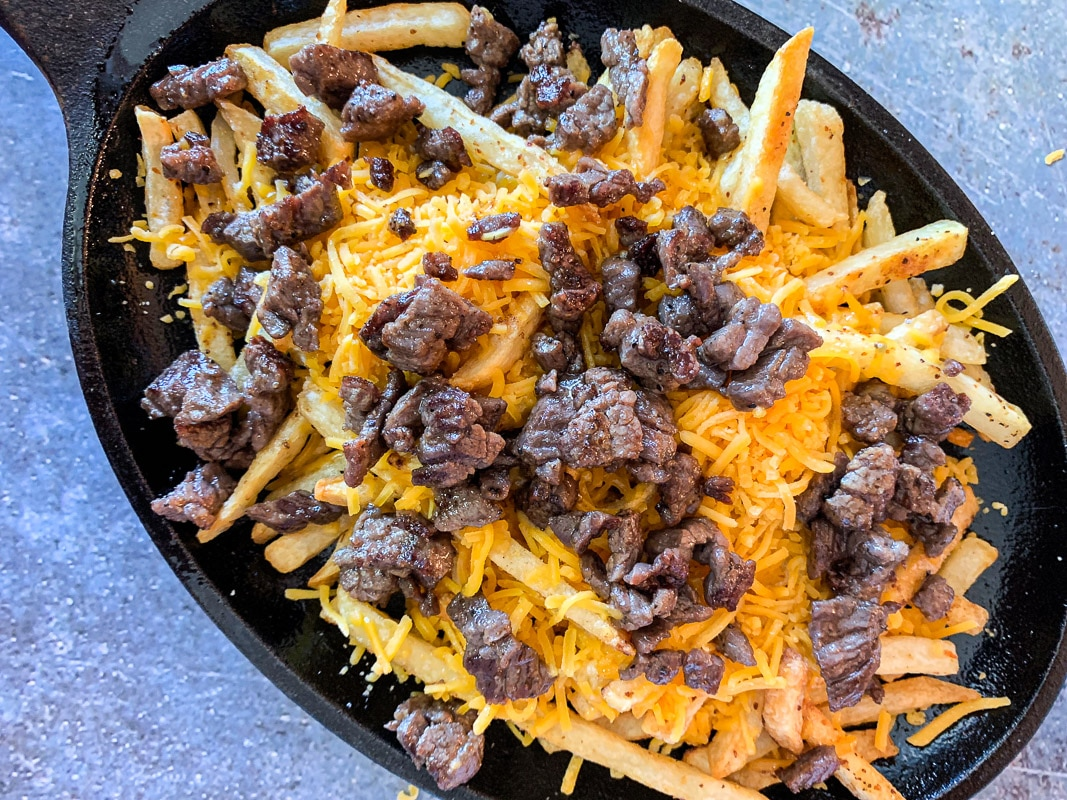 fries in a pan, covered in cheese and diced Carne Asada meat
