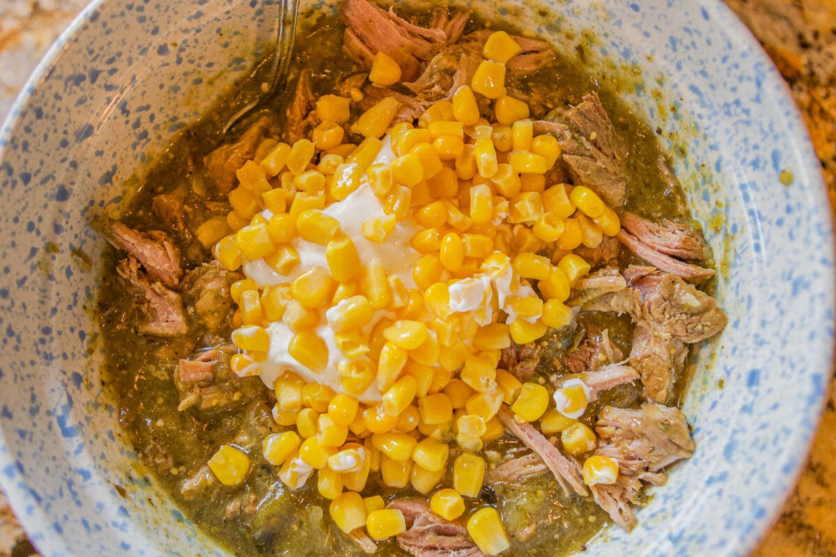 chili verde with corn and sour cream in a bowl