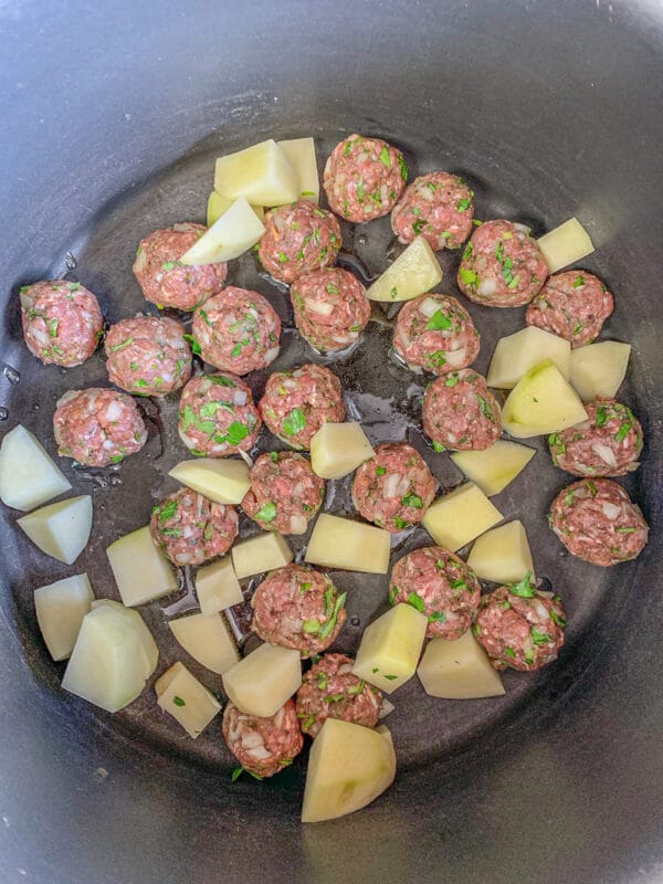 raw meatballs and cubed potatoes in a pot