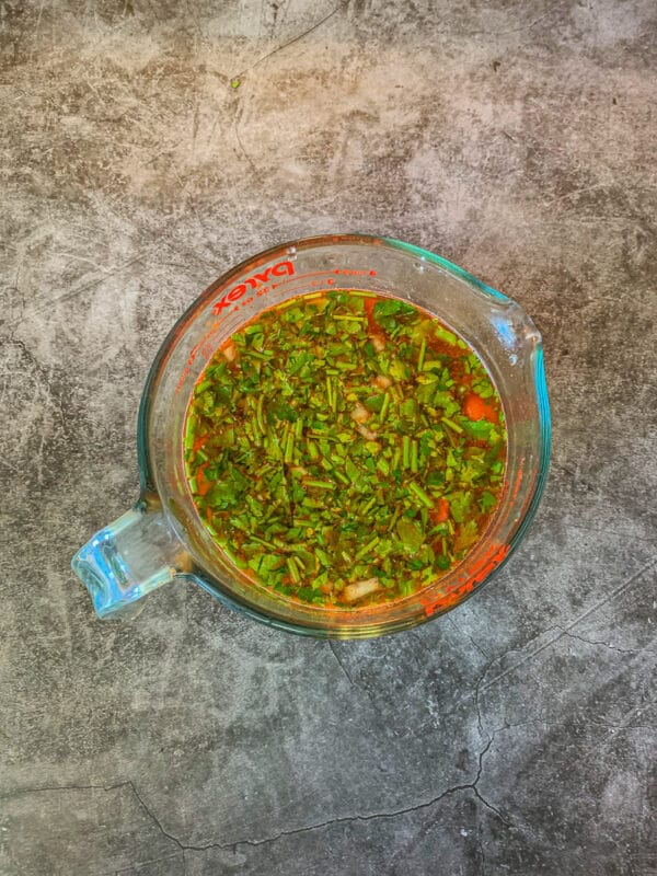 tomato sauce with diced parsley in a large measuring cup