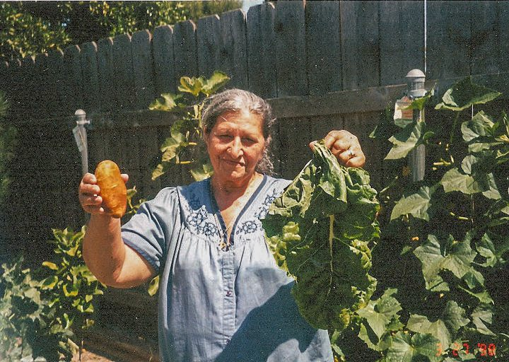mom in the garden holding spinach and potato