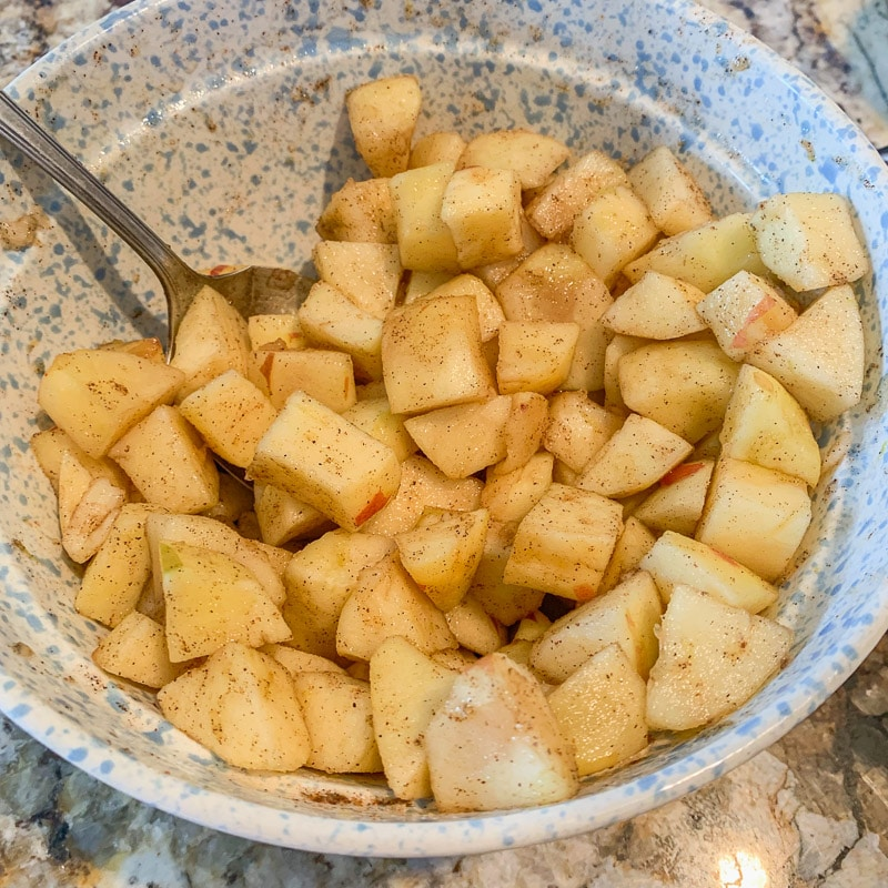 diced apples with spices in a blue bowl