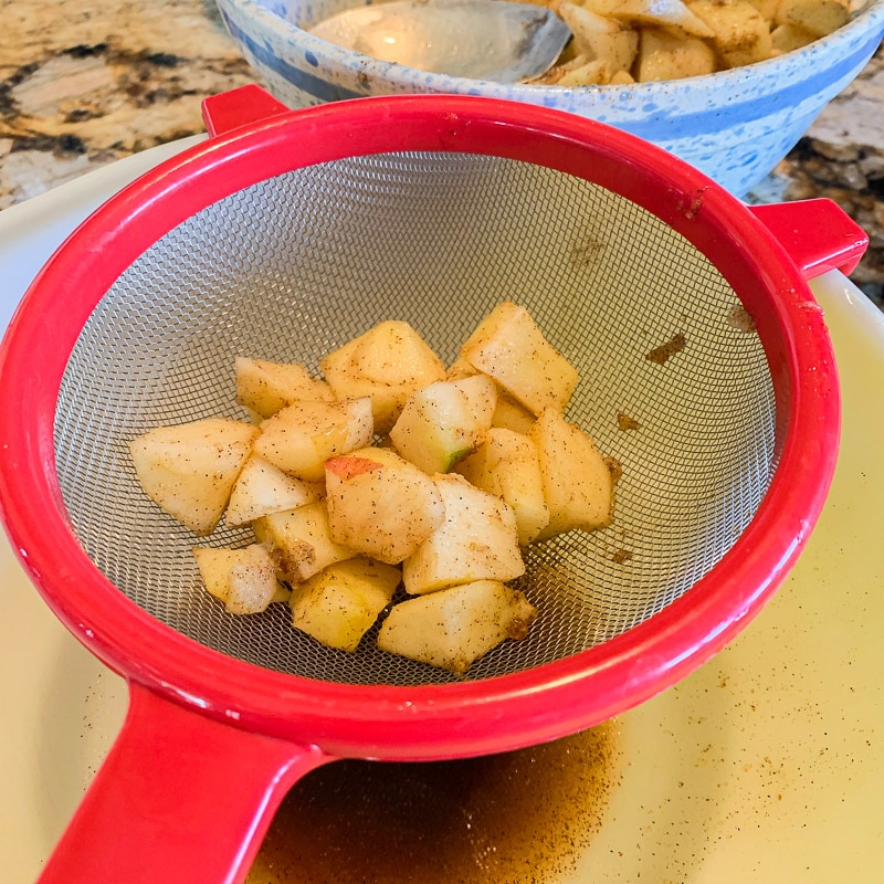 diced apples in a red strainer over a bowl