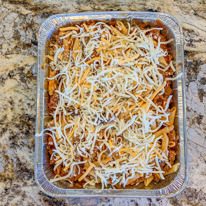 pasta with sauce topped with shredded cheese in a lasagna  pan