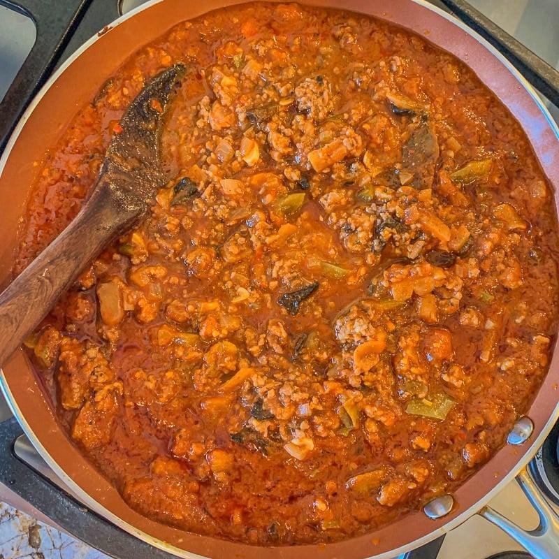 stirring pasta meat sauce in a pan
