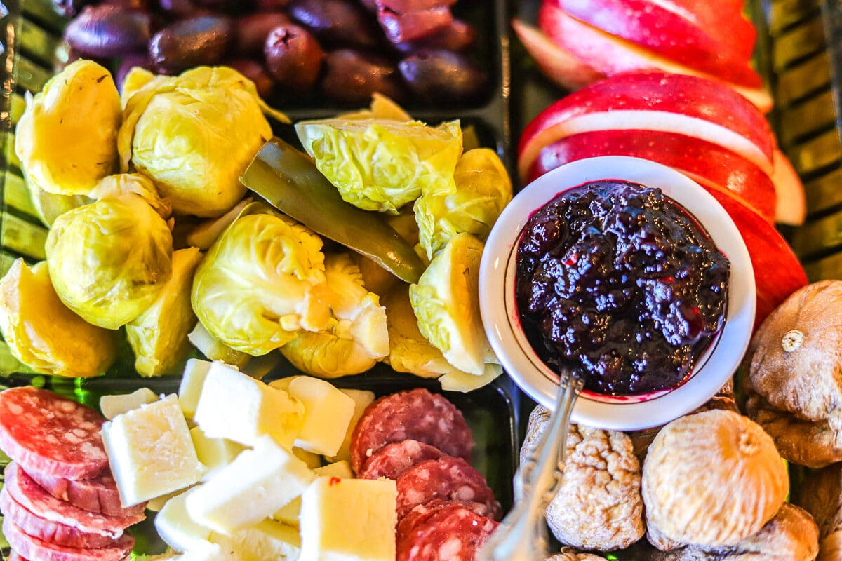charcuterie board with various fruits, pickles, jam