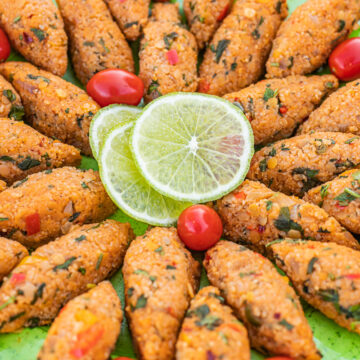 vegan kibbeh on a green plate with cherry tomatoes and sliced lime