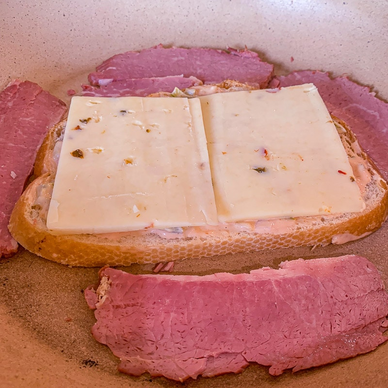 bread with cheese and corned beef in a pan