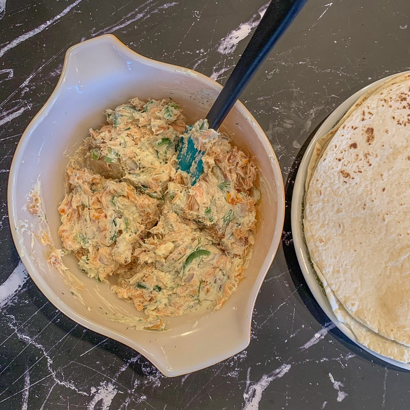 smoked salmon filling in a bowl with tortillas on the side