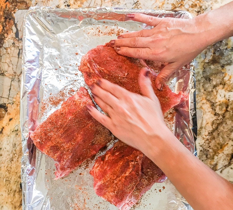working dry rub into raw ribs