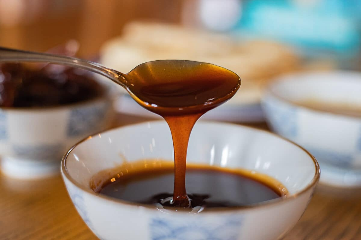 date syrup being spooned out of a bowl full of date syrup