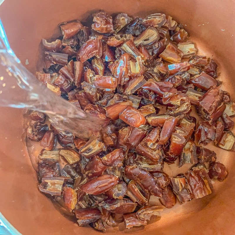 pouring water on chopped dates in a pot