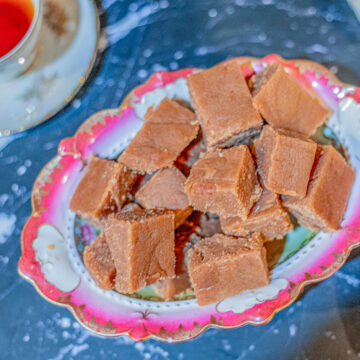 halwa in a bowl with a pink rim with cup of tea on the side