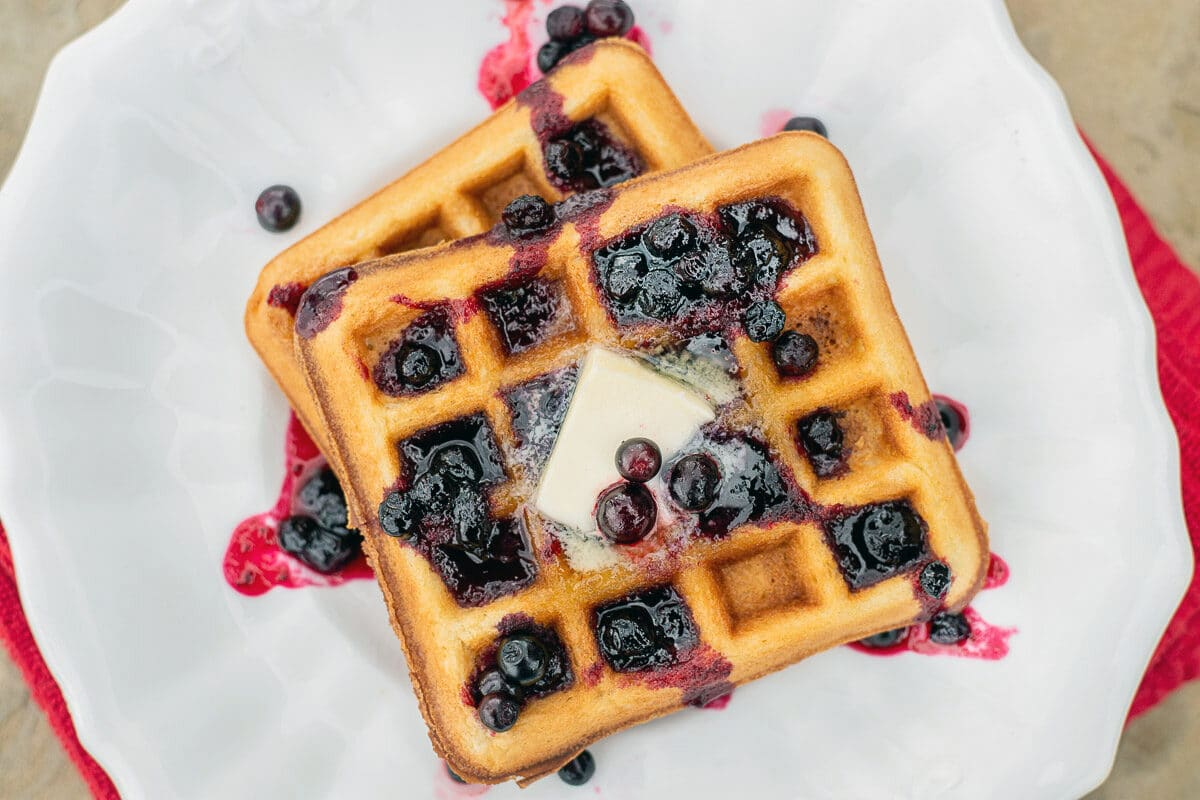 waffles with huckleberry syrup on a white plate