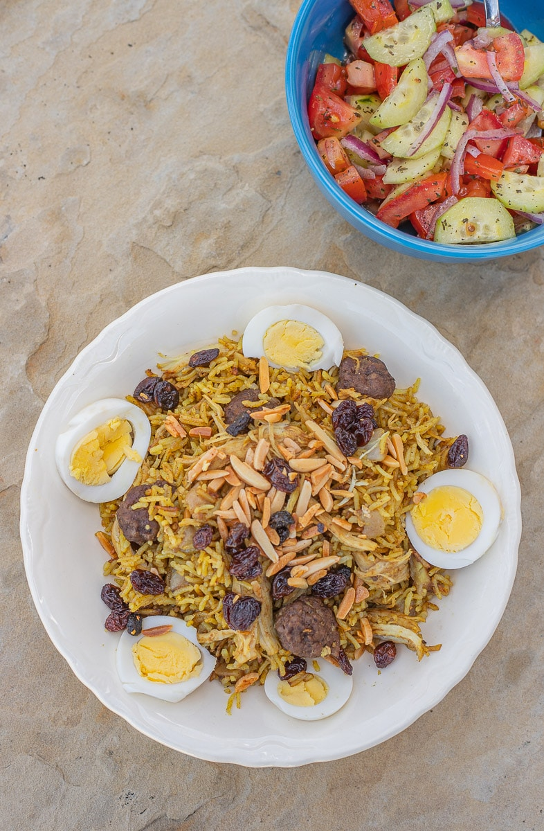 biryani in a white plate with a salad in a blue bowl
