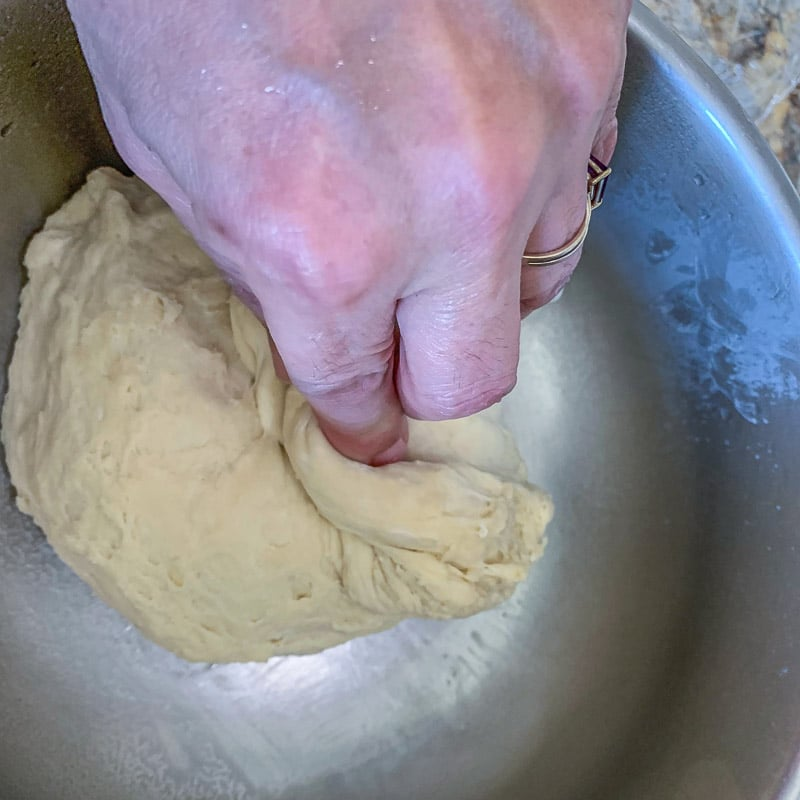 folding dough over in a bowl
