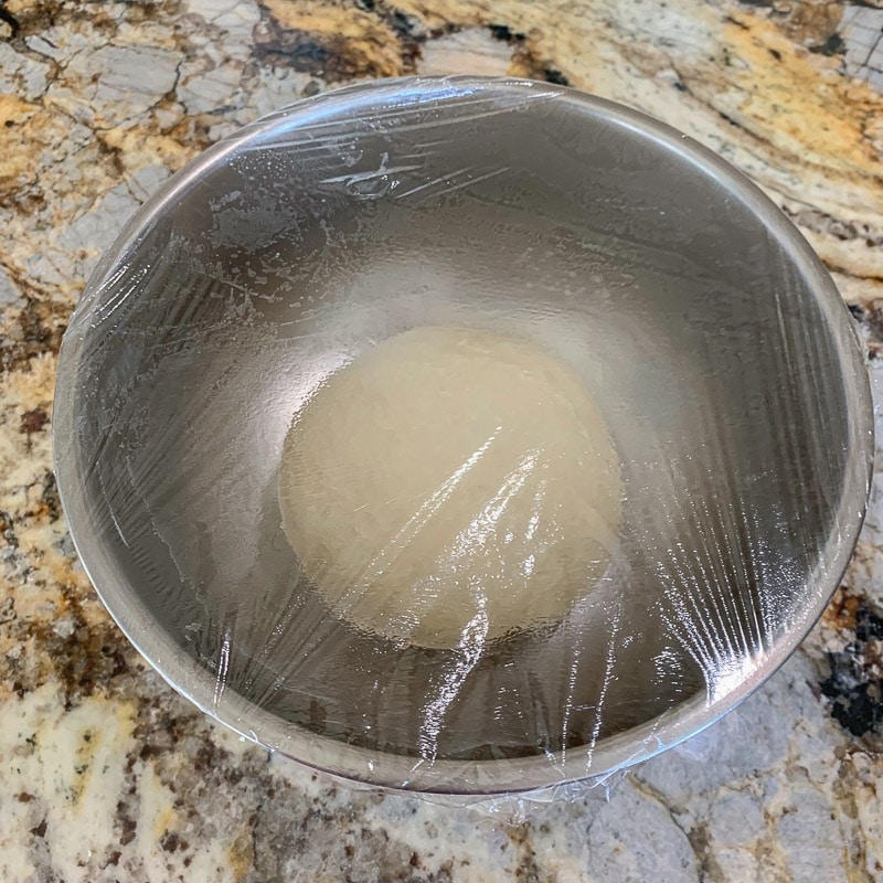 smooth dough in a bowl covered with Saran Wrap