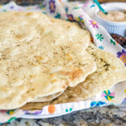 lavash bread on a flowered dish cloth with other fixings in the background
