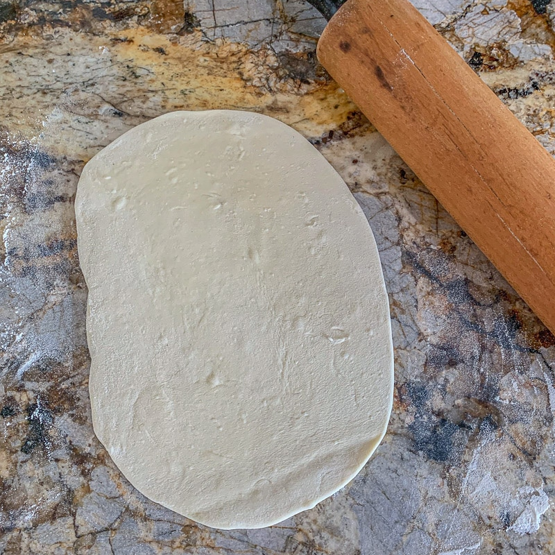 lavash bread dough rolled out on counter with a rolling pin