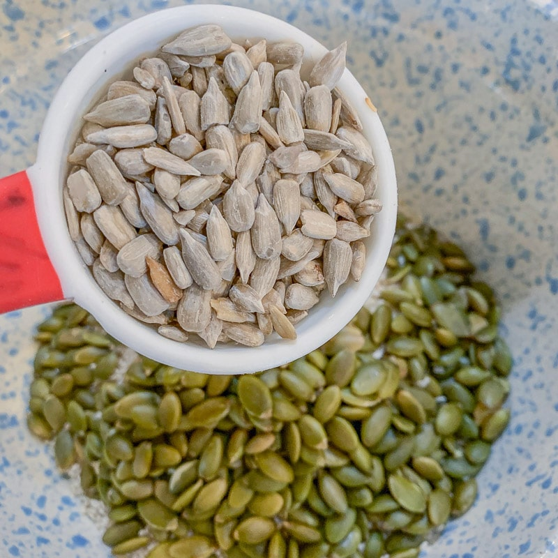 adding sunflower seeds to a bowl