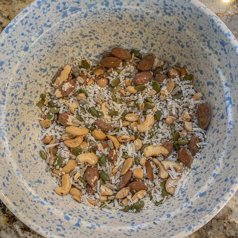 seeds and nuts, and shredded coconut in a spotted bowl