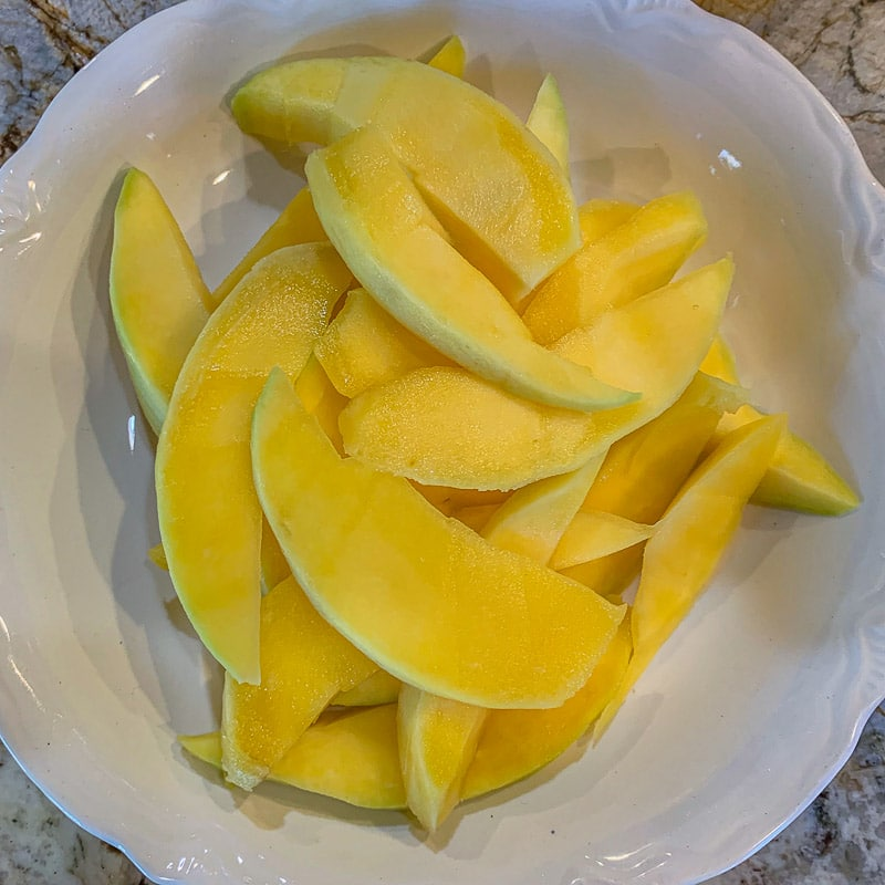 sliced mangos in a white bowl