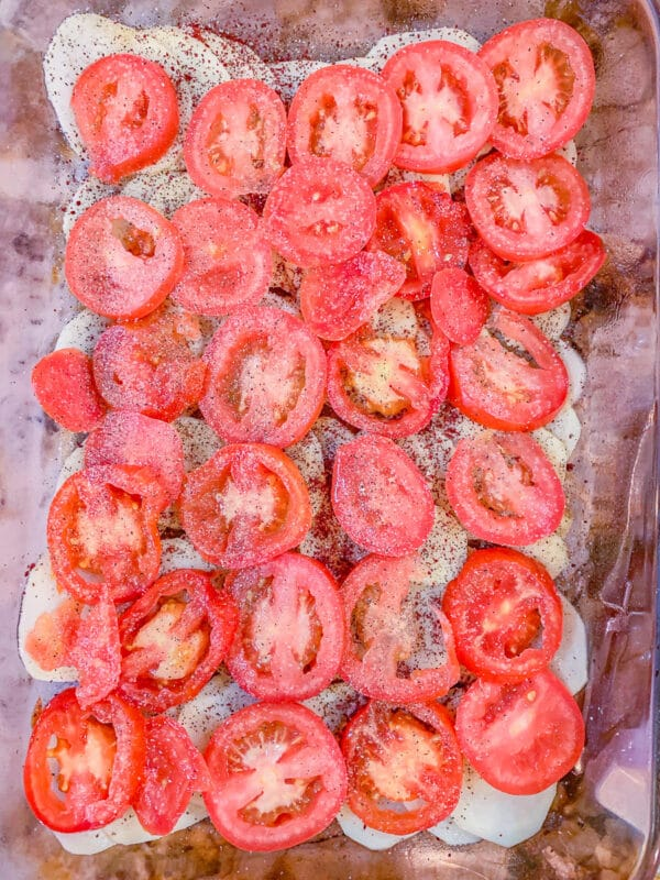 sliced tomatoes over other ingredients in a casserole dish