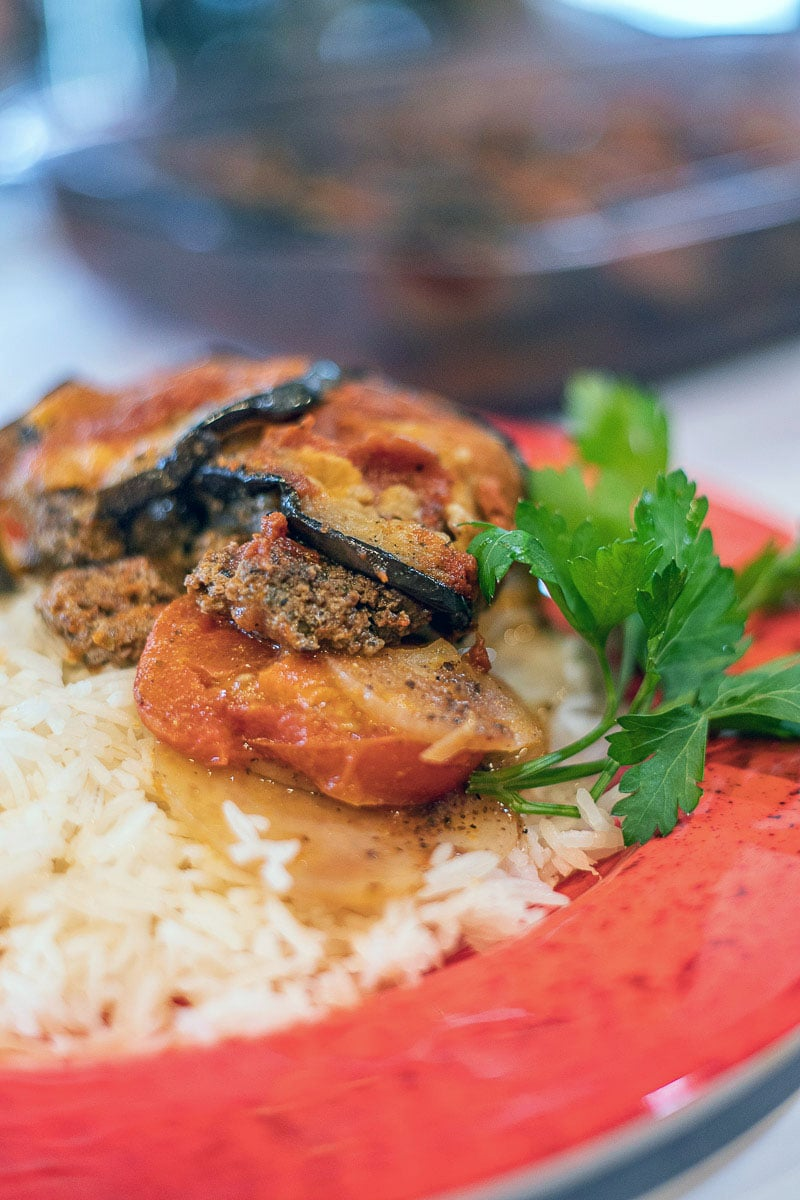Tespi (eggplant casserole) on white rice served on a red plate
