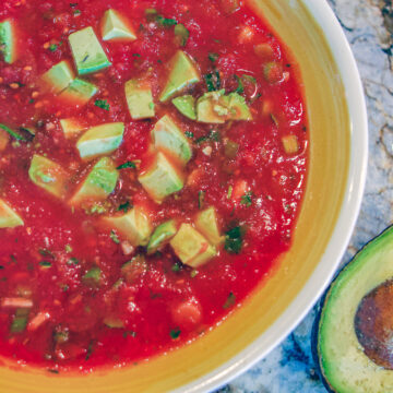 mexican salsa in a bowl with a yellow rim and a sliced avocado on the side