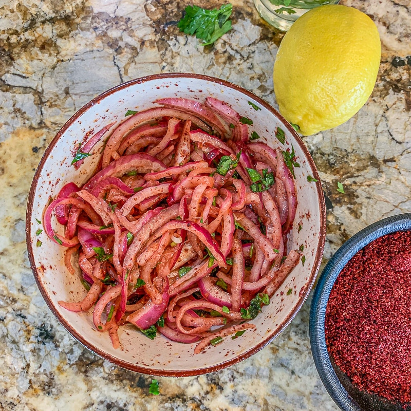marinated sumac onions in a bowl with lemon and sumac on the side